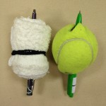 Rolled up wash cloth and tennis ball, each with a pen stuck through them
