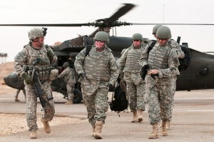 Men in camouflage walk away from a helicopter