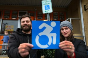 Brian Glenney and Sara Hendren holding the new wheelchair sign in front of the old one
